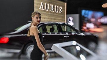 Девушка у автомобиля Aurus Senat на Московском международном автомобильном салоне 2018