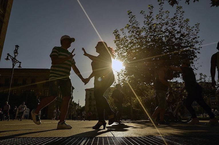 Люди танцуют осенним вечером в Памплоне на севере Испании
