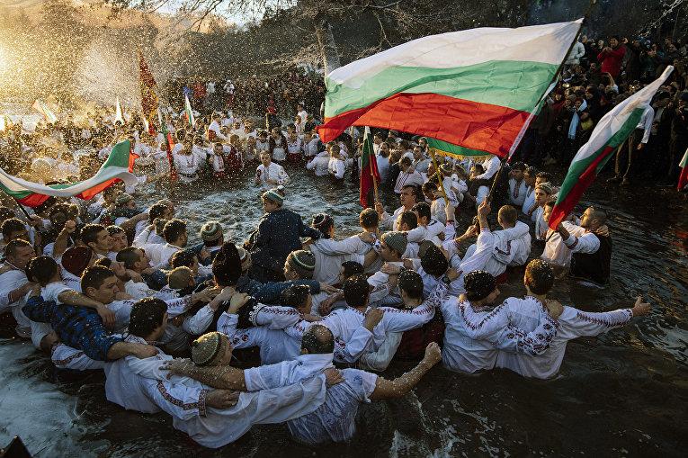 Верующие танцуют в холодных водах реки Тунджа во время дня Богоявления в городе Калофер, Болгария