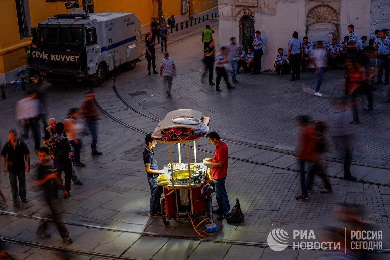 Продавец вареной кукурузы и полицейские на улице Истикляль возле площади Таксим