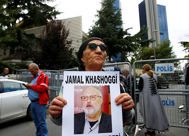 Борец за права человека держит портрет журналиста Джамаля Хашогги во время протестов у консульства Саудовской Аравии в Стамбуле, Турция