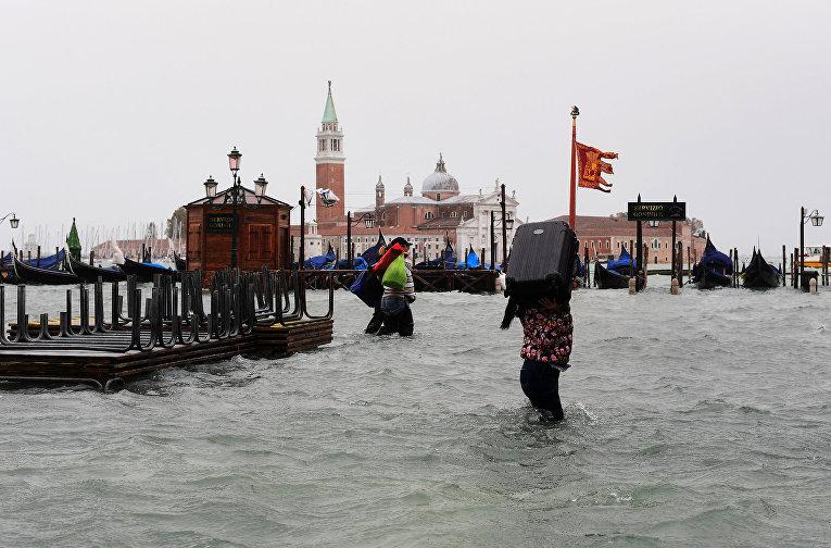 Женщина несет чемодан на затопленной площади Святого Марка в Венеции