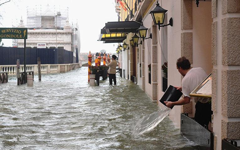 Сотрудник заведения вычерпывает воду