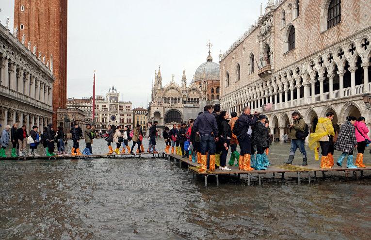 Люди гуляют по подиуму на затопленной площади Святого Марка