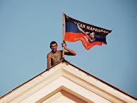 Ополченец Донецкой народной республики (ДНР) устанавливает флаг ДНР на здании мэрии города Комсомольское Донецкой области