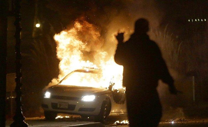 Подожженный автомобиль полиции во время беспорядков в Фергюсоне