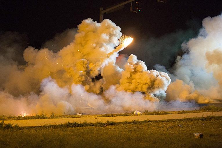 Протестующий кидает дымовую шашку во время столкновений с полицией в Фергюсоне