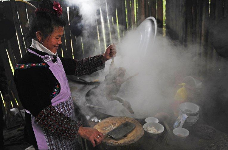 Представительница народности Миао готовит угощение к празднику «Гузанг»