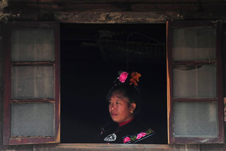 Представительница народности Миао ждет гостей в первый день праздника «Гузанг»