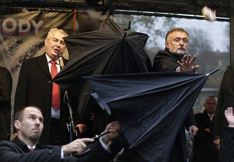 Охранники закрывают Милоша Земана от летящих в него яиц, томатов и бутербродов