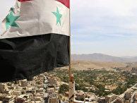 Флаг Сирии в городе Маалула к северу от Дамаска