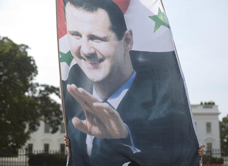 Плакат с президентом Сирии Башаром Асадом на демонстрации у Белого дома