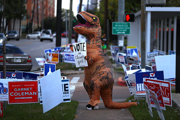 Человек в костюме динозавра призывает людей голосовать на промежуточных выборах в Хьюстоне, штат Техас