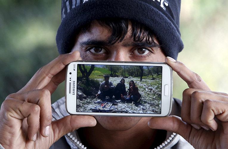 Беженец Асам из города Пирмам показывает фотографию своих родителей и сестры