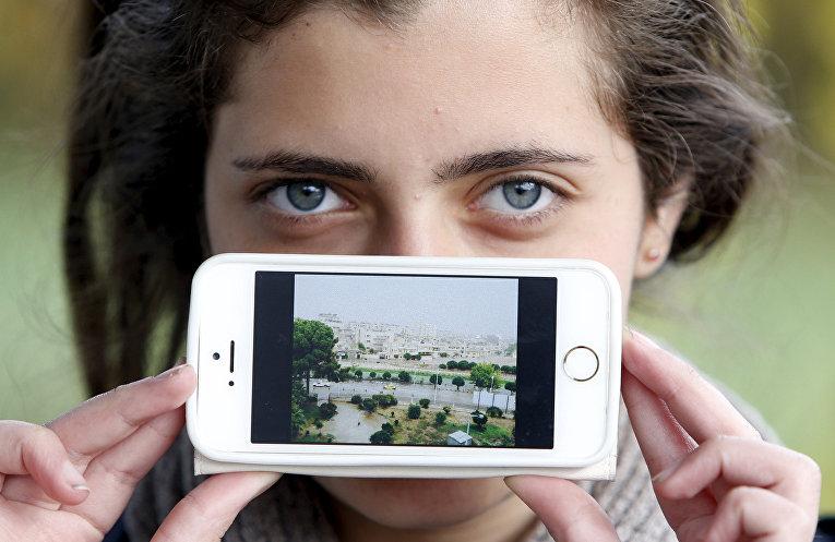 Беженка Хая из Сирии показывает фотографию своего родного города