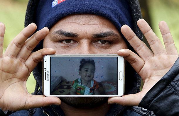 Назар, беженец из города Басра в Ираке, показывает фотографию своей дочери Шехед