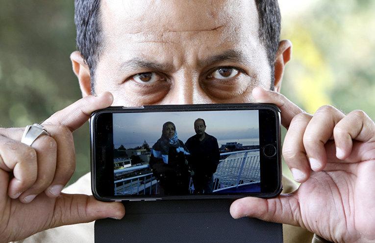 Абдулла, беженец из Багдада, показывает фотографию, на которой он запечатлен вместе со своей женой