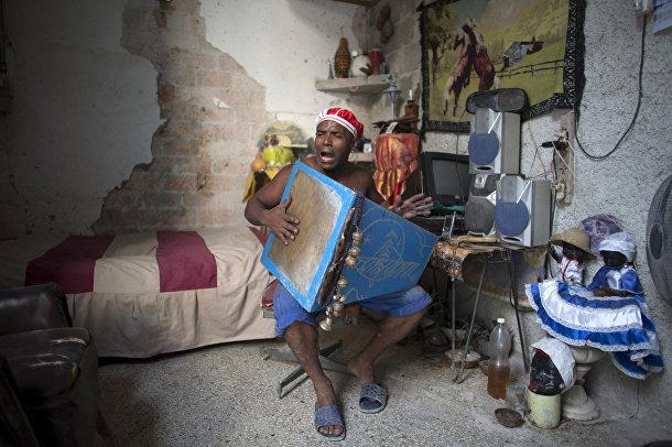 Последователь сантерии Мигель Анхель поет религиозные песни в своем доме в Гаване