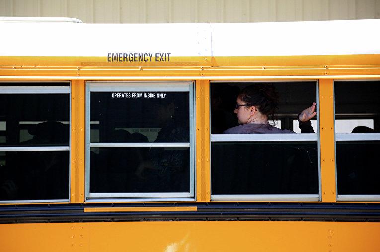 Студенты ждут в автобусе возле колледжа в Орегоне, после того, как там произошла стрельба