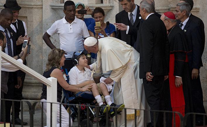 Папа Франциск разговаривает с мальчиком на инвалидной коляске во время встречи с молодежью в Гаване