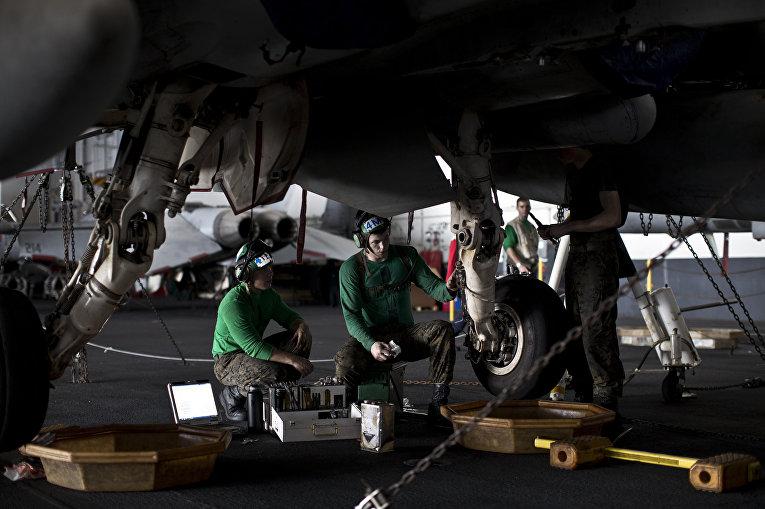 Авиамеханики ремонтируют шасси реактивного истребителя на борту авианосца «Теодор Рузвельт»