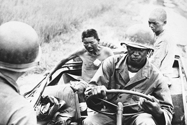Американские солдаты везут пленных северокорейцев в госпиталь