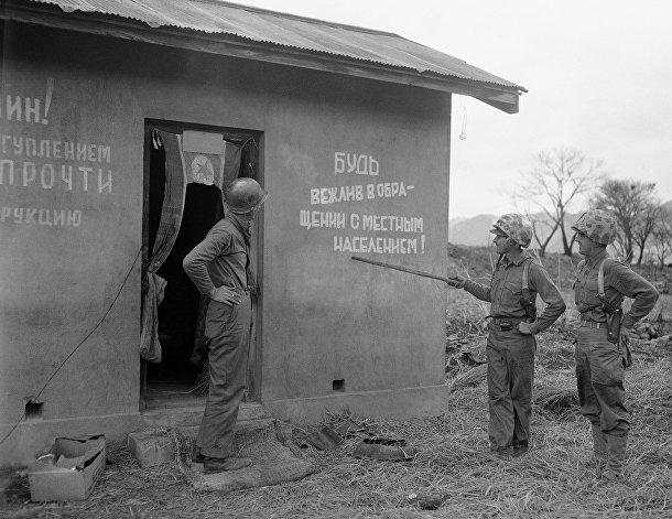 Американские солдаты у корейского домика с надписями на русском на стенах