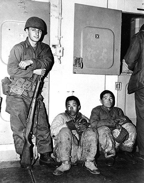 Солдат морской пехоты с северокорейскими военнопленными