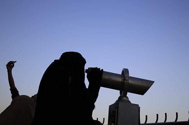 Женщина смотрит в бинокль на смотровой площадке Каирской телебашни
