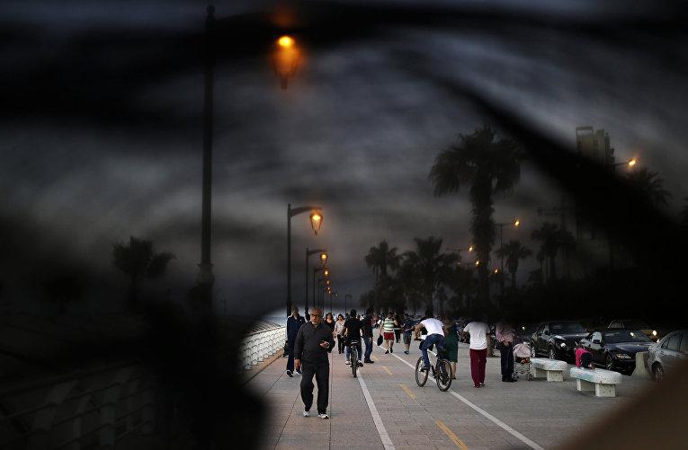 Люди идут по набережной в Бейруте, фотография сделана через никаб