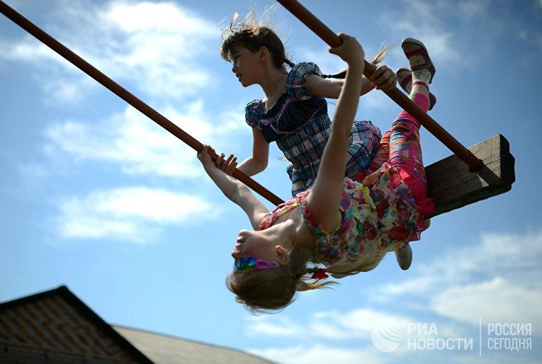 Дети качаются на качелях на пришкольной площадке в селе Иванкино Новосибирской области