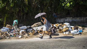 Девушка с зонтом идет мимо помойки
