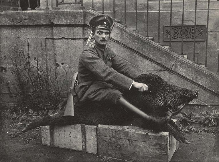 Офицер авиации Германии позирует с чучелом кабана рядом с домом у Западного фронта