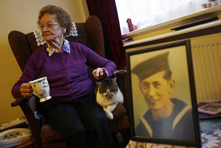 Мэри Барбер у портрета своего мужа, вернувшегося со Второй мировой войны, в дважды благословенной деревне Фликсборо