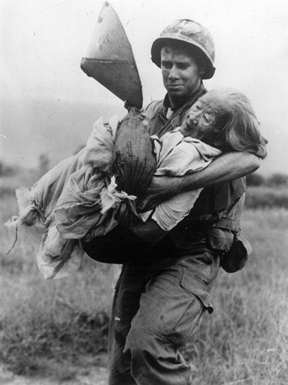 Американский солдат несет пожилую вьетнамку к вертолету для эвакуации в лагерь для беженцев