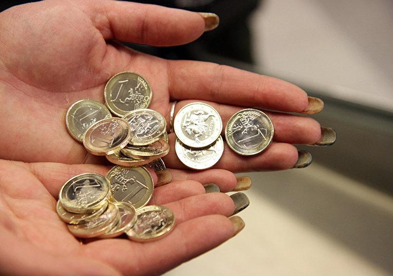 Кассир считает монеты в вильнюсском супермаркете в Литве