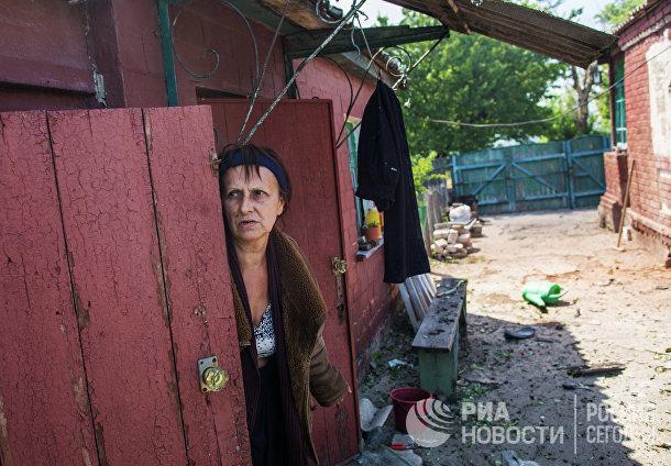 Женщина выглядывает из убежища после массированного артиллерийского обстрела поселка Черевковка под Славянском