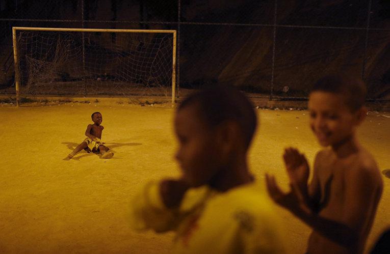 Дети отдыхают после футбольного матча в трущобе Сао-Карлос в Рио-де-Жанейро