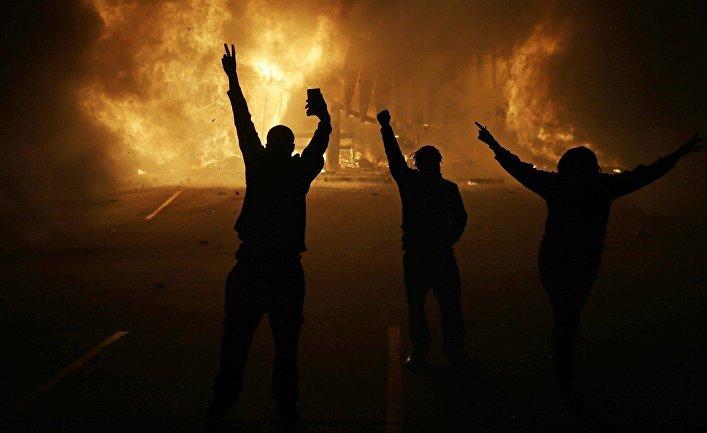 Протестующие смотрят на горящие здания магазинов