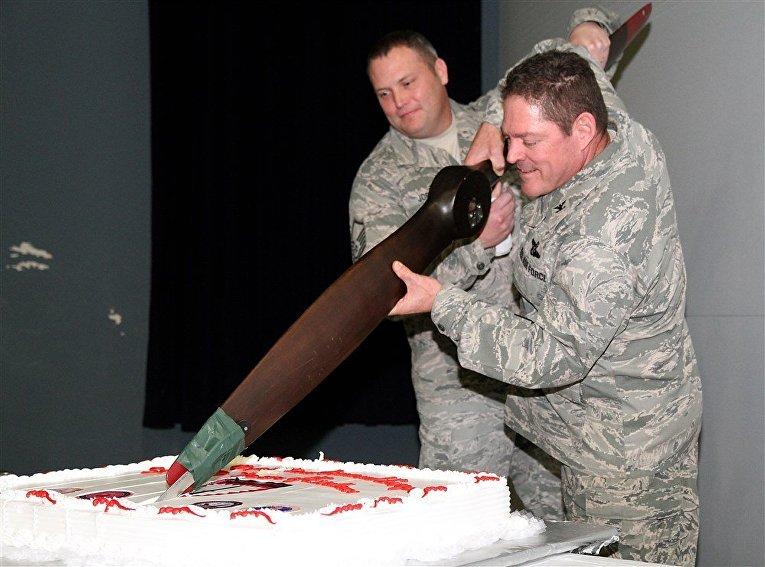 Два военнослужащих ВВС США режут торт пропеллером от аэроплана, 59-я годовщина Европейского командования сил специальных операций
