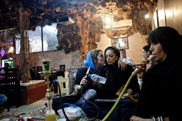 Молодые женщины курят кальян в кафе в Тегеране