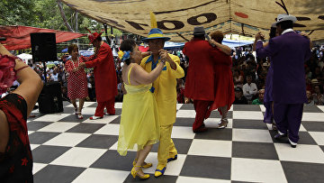 Мужчины в костюмах в стиле пачуко танцуют с женщинами, одетыми в стиле румберас
