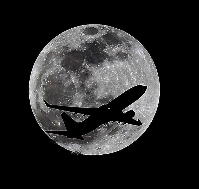Силуэт самолета на фоне луны за час до полного лунного затмения