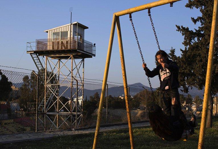 Дети играют у забора, отделяющего буферную зону ООН на Кипре