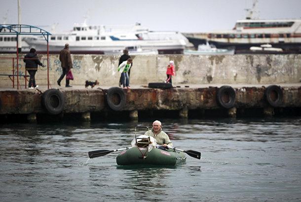 Человек плывет на лодке рядом с набережной в Ялте