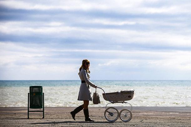 Женщина с коляской идет по набережной в городе Алушта