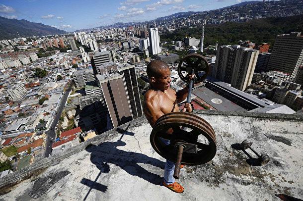 Житель небоскреба «Башня Давида» в Каракасе поднимает штангу на балконе на 28-м этаже