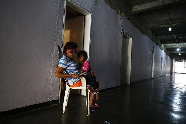 Женщина с внучкой разгадывают кроссворд в коридоре небоскреба «Башня Давида» в Каракасе