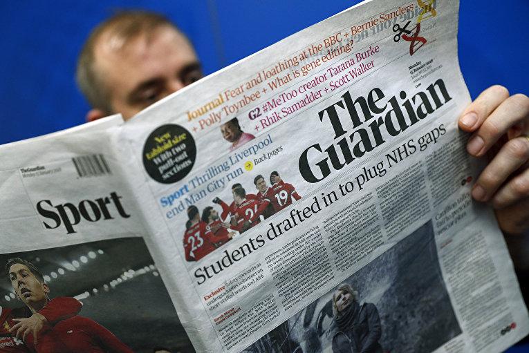 Мужчина читает газету The Guardian в Лондоне