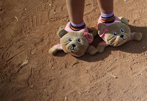 Игрушечная обувь на ногах ребенка из каравана мигрантов, направляющихся из Центральной Америки в США